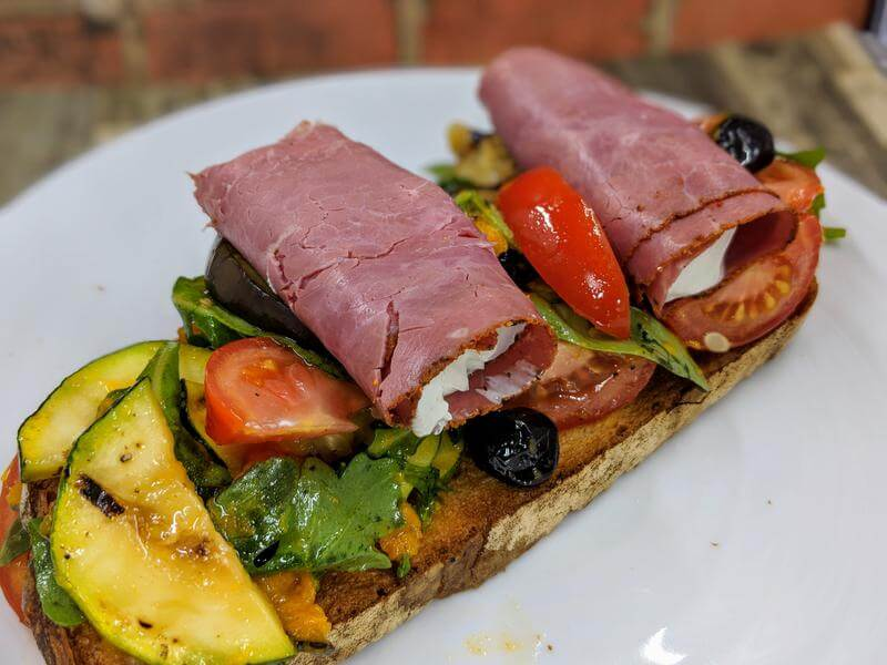 Grilled vegetable open sandwich with pastrami roll-ups